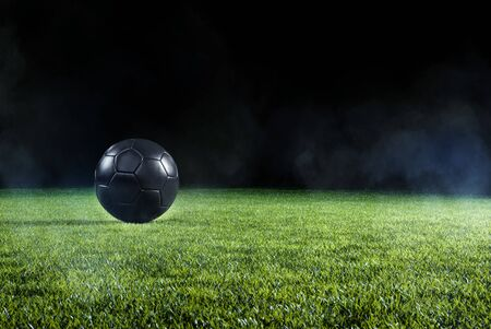 Black Football on an illuminated empty sports field at night backlit by bright spotlights in a low angle view with shadow, mist and copy space
