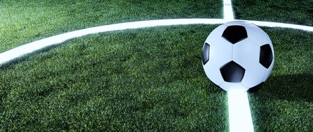 Soccer ball on glowing lines on a green grassy sports field at night in a panorama banner with copy space for sports or football themes Фото со стока