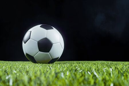 Traditional football on an illuminated empty sports field at night backlit by bright spotlights in a low angle view with shadow, mist and copy space Stockfoto