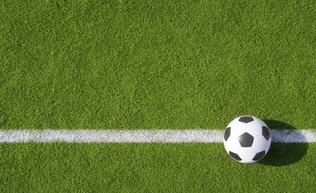 Championship football or soccer ball on a green sports field placed on a white line on the turf in evening light with copy space