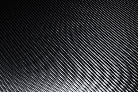 Structural detail of industrial carbon fibre sheet showing diagonal pattern as light plays across the surface in a background texture