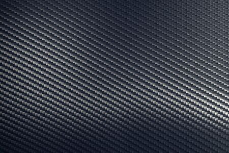 Diagonal oriented grey woven carbon fibre composite texture. Sheet of future light raw material. Modern technology and material concept...