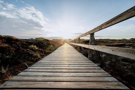 Colorful view of seaside landscape before sunset. Low view of Wooden touristic walkway with railing leading to sun. Summer vacation and wildlife concept.