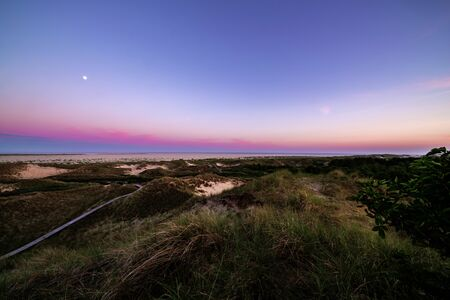 Wooden promenade stretches along edge of coast at sunset with amazing colourful purple sky over hilly sand dunes and coastal vegetation. Summer vacation, holiday at sea concept.  Фото со стока