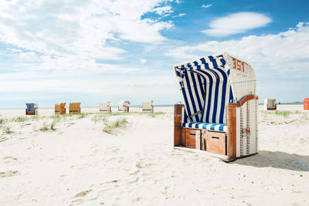 Blue and white striped wooden wicker chair or bench on a white sandy tropical beach in hot summer sunshine in a travel and vacation concept
