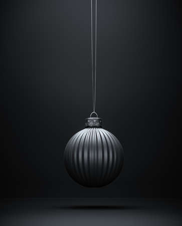 Christmas ball hanging on string. Vertical striped Christmas ornament against dark shaded background. Black and white. Christmas decoration, festive atmosphere concept.