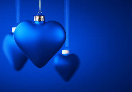 Group of three matt blue Christmas ornaments in heart shape. Baubles hanging on thread against royal blue background. Christmas decoration, festive atmosphere concept. Copy space. 免版税图像