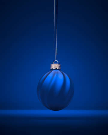 Royal blue Christmas ball hanging on silver string. Christmas ornament decorated with twisted stripes. Christmas decoration, festive atmosphere concept. 免版税图像