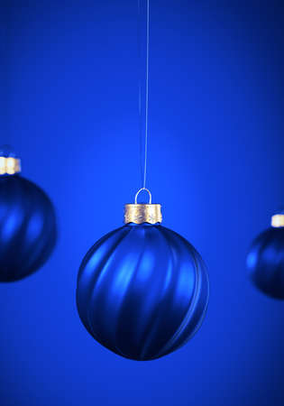 Twisted striped Christmas balls hanging against blue shaded background. Christmas decoration, festive atmosphere concept. Selective focus, portrait orientation.