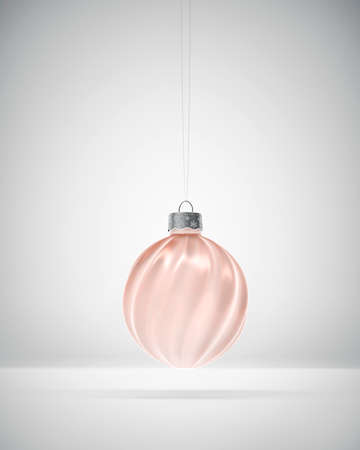 Light bronze twisted ribbed Christmas ball hanging over white background. Diffused light. Christmas decoration, festive atmosphere concept.