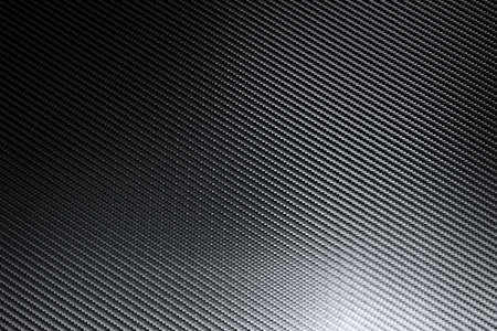 Gray woven carbon fiber sheet surface with light reflection. Texture and grid pattern background. Composite raw material. Modern technology and material concept.