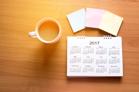Travel Planning on Calendar and use note with a cup of coffee on a wooden table Foto de archivo