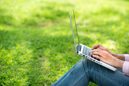 Young Asian beautiful woman with smiling face working outdoor in a public park. Working on laptop outdoors. Cropped image of female working on laptop while sitting in a park.