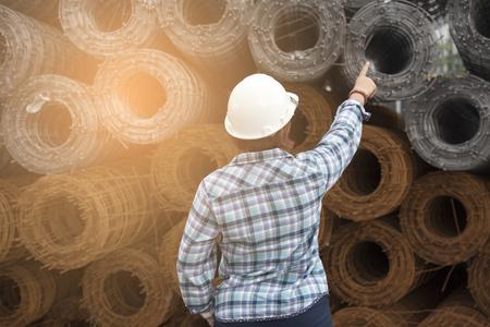 Ingénieur femme porter une chemise bleue et un casque blanc sur un fond industriel.