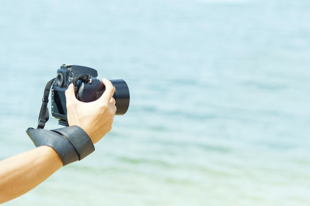 Professional camera in man hands on the beach. Imagens
