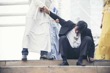 Failure businessman going bankrupt try to stand up when a friend are helping.