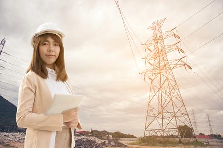 Jeune femme intelligente d'ingénieur électrique travaillant à l'aide d'une tablette pour vérifier les réseaux électriques à l'usine électrique.