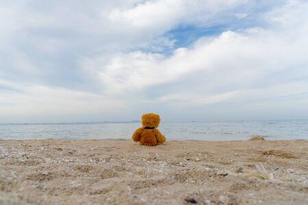 Teddy Bear alone on the beach with the blue sky. Travel concept.