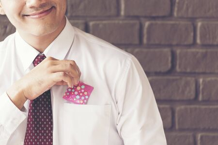 Sexy man smiling holding condom from his pocket. Safe sex Concept. Stock Photo - 128035386