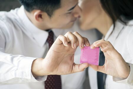 Couple lover showing condom on hand. Safe birth control concept.