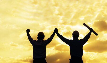 Silhouette des Erfolgsingenieurs, der bei Sonnenuntergang mit Victory-Zeichen die Hände zusammenhält. Der Erfolgsingenieur trägt zusammen einen gelben Helm zur Sicherheitsberatung. Baukonzept.