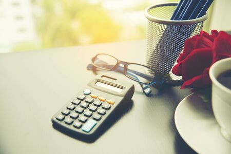 Business stuff with pencil, calculator, red rose, cup of coffee , stationery set.