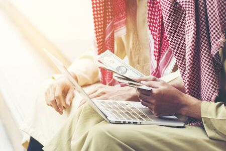 Handsome greedy arab man showing money on hands and counting money. Financial corruption Concept. Archivio Fotografico