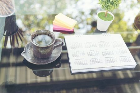 Calendar 2018 Appointments Schedule place on grass table with bohkeh and light on background. colorful sticky notes and cup of coffee for planner. Imagens