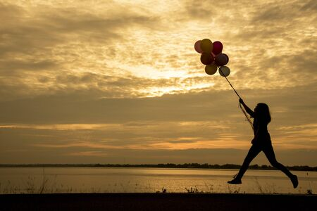 Silhouette woman holding air balloons standing and see the lake on the sunset Imagens