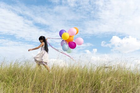 Happy woman jumping with air balloons on the meadow. Imagens