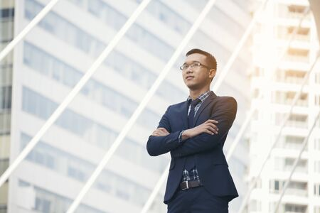 Leader young executive businessman standing in modern city background to show powerful and leadership. Business Leader Conceptual Image.