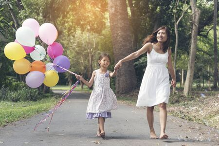 Adorable cute girl holding hands together with colorful balloon.