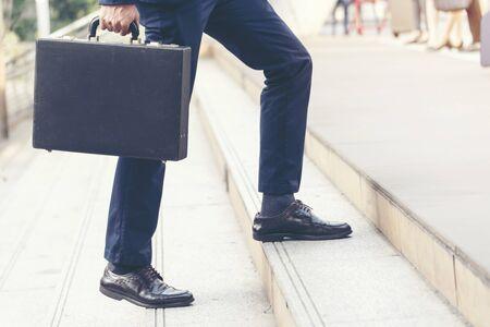 Jeunes gens d'affaires actifs qui montent les escaliers pour aller travailler dans une ville moderne. Groupe bondé de personnes dans le mode de vie des grandes villes avec mallette, téléphone intelligent, tasse de café. Concept de mode de vie d'entreprise.
