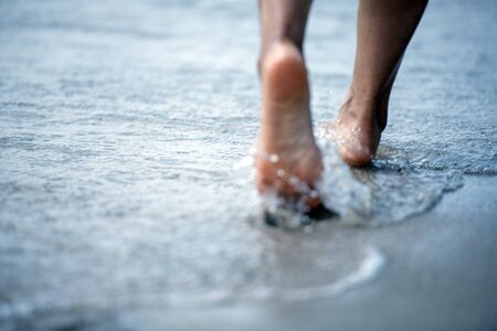 Woman bare foot walking on the summer beach. close up leg of young woman walking along wave of sea water and sand on the beach. Travel Concept.
