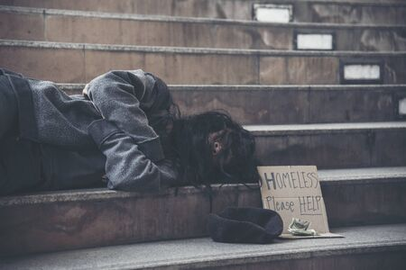 Homeless people poverty beggar man asking for money job and hoping help in helpless dirty city sitting with sign of cardboard box said Homeless Please Help on board. Beggar in city concept.