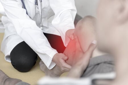 Exercise injury. Doctor help patient who had knee to release pain. Healthcare concept.