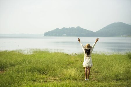 Back side woman feeling fresh freedom positive energy standing grass field flower meadow international woman's day 8 march. Cheerful morning relaxation springtime mountain view with sunlight Stock fotó