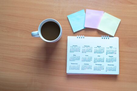 Travel Planning on Calendar and use for note with a cup of coffee on a wooden table