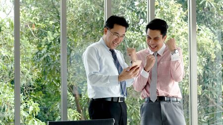 Success Businessman happy got good news from mobile smart phone that business so success. Asian young business man raise hand with happiness, smiling, excited after got great news from phone. Archivio Fotografico