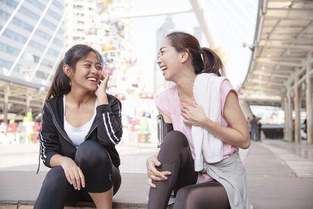 アジアスポーツフィットネス現代都市でエクササイズをしているアジアスポーツフィットネス女性は、外でウェルネススポーツウェアを着用しています。若い女性は屋外で明るい晴れで運動をする運動をします。健康的な健康ライフスタイル女性の概念。