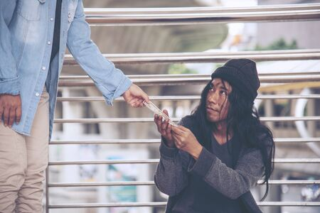 Woman helping hands to homeless people poverty beggar man holding hands asking for money job and hoping help in helpless dirty city sitting on streets. Desperate Beggar in city concept. 版權商用圖片