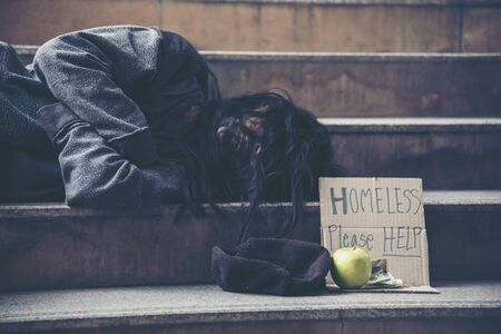 Homeless people poverty beggar man asking for money job and hoping help in helpless dirty city sitting with sign of cardboard box said