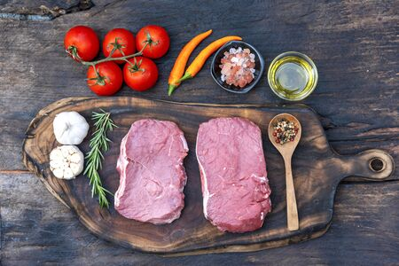 Raw meat beef steak organic fresh ingredient on wooden board table background in kitchen with rosemary, salt, garlic, tomato, black pepper, olive oil. Meat beef on wooden plate for beefsteak raw meat 版權商用圖片