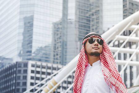 Handsome modern Arabian man standing in modern city wear muslim dress headscarf eastern ethnic smile outside office. Arab Man looking plan new project while walking in big city. Business successful