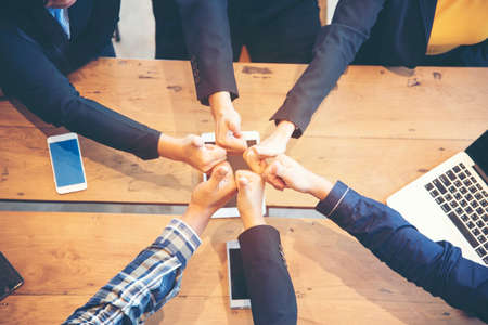 Communication unified concept.Team Business Partners Giving Thumb up Bump after Complete a deal. Successful Teamwork Partnership in an office. Businessman with hands together.