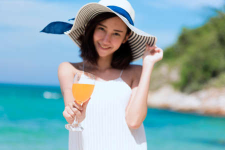 Summer time woman vacation on the beach. Cheerful woman wear summer dress and straw hats sitting on the beach look at sea. Time to relax in summer lifestyle outdoor shot on tropical island beach.