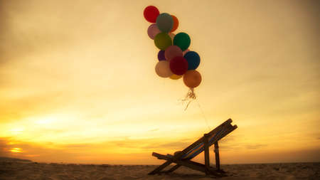 Silhouette balloon on the beach during the sunset in summer time. multicolored of balloon holding on seat.