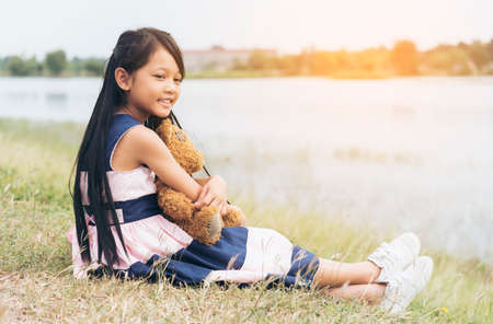 Happy Child hug teddy bear in green park playground. Teddy bear best friend for little kids cute girl. Autism happy funny playing together on playground in happiness family feel love and warm hugs Stock Photo