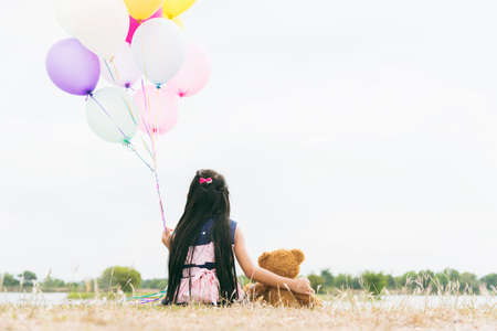Happy Child hug teddy bear hold air balloon in green park playground. Teddy bear best friend for little kids cute girl. Autism happy playing together holding colorful helium balloons on playground