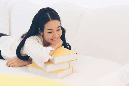 Young Asian Woman student university holding text book on her hands sitting on sofa with colorful pillow. Study hard to get a better grade. Education Concept